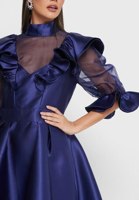 فستان أزرق من القماش الممتاز من نوع ستان , يتميز هذا الفستان من نسيج املس ومريح بملمس الساتان عالية الرقبة كما يحتوي هذا الثوب الراقي من اكمام بالون شفافة مع اساور كشكش مع تداخلات كشكش اسفل الياقة , تألقي و تميزي سيدتي مع هذا الفستان المميز الميدي بحواف فلير , كوني أنت ملكة هذه الحفلة يحتوي أيضا على سحاب مخفي في الخلف .